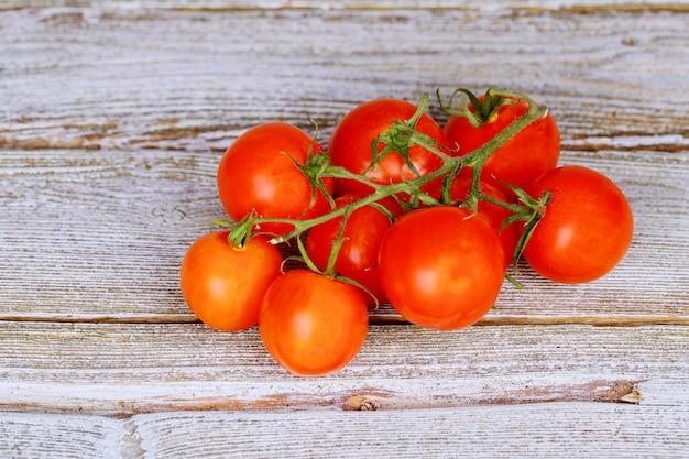 Tomates vermelhos frescos em um fundo de placas antigas
