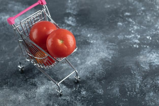Tomates vermelhos frescos em um pequeno carrinho de compras