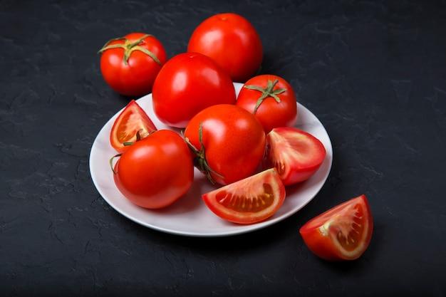 Tomates vermelhos frescos em um prato branco. close-up, copie o espaço.