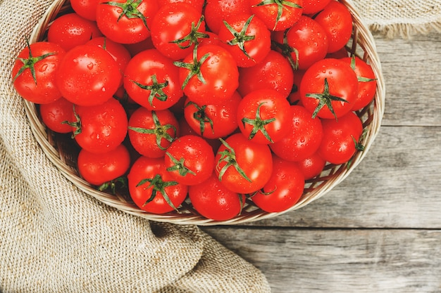 Tomates vermelhos frescos em uma cesta de vime em uma tabela de madeira velha. tomates de cereja maduros e suculentos com gotas da umidade, tabela de madeira cinzenta, em torno de um pano da serapilheira. em estilo rústico.