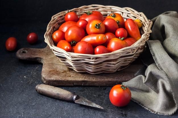 Tomates vermelhos frescos em uma cesta de whicker em fundo preto.
