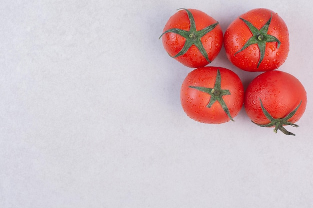 Tomates vermelhos frescos na mesa branca.