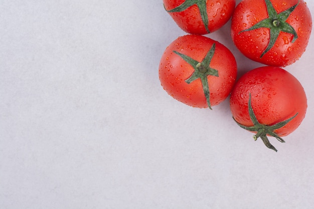 Tomates vermelhos frescos na superfície branca