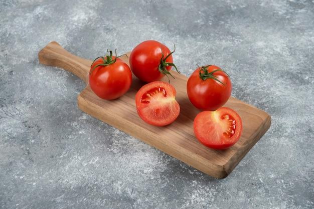 Tomates vermelhos grandes e frescos em um fundo de mármore.