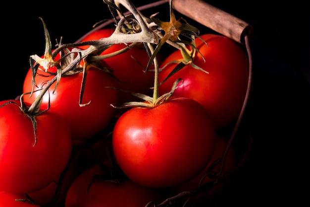 Tomates vermelhos grandes no fundo preto na obscuridade clara pronta para cozinhar