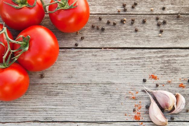 Tomates vermelhos húmidos com pimenta e alho na velha mesa de madeira