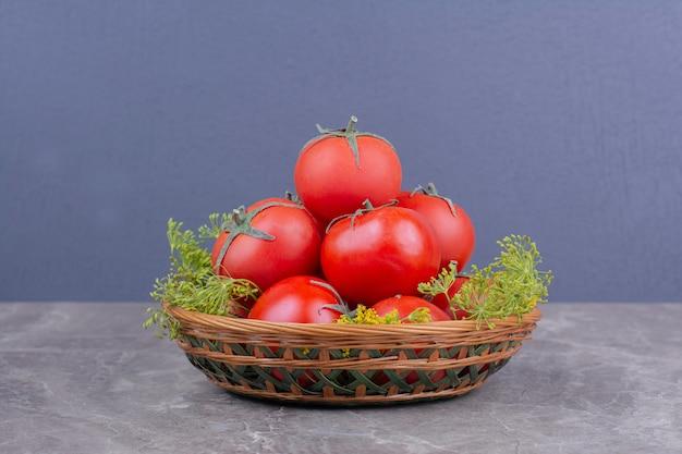 Tomates vermelhos isolados em um prato de madeira