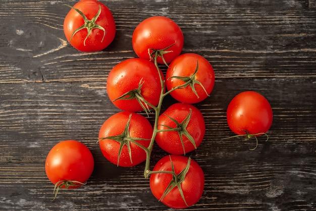 Tomates vermelhos maduros inteiros em um galho em um fundo preto. vista do topo.