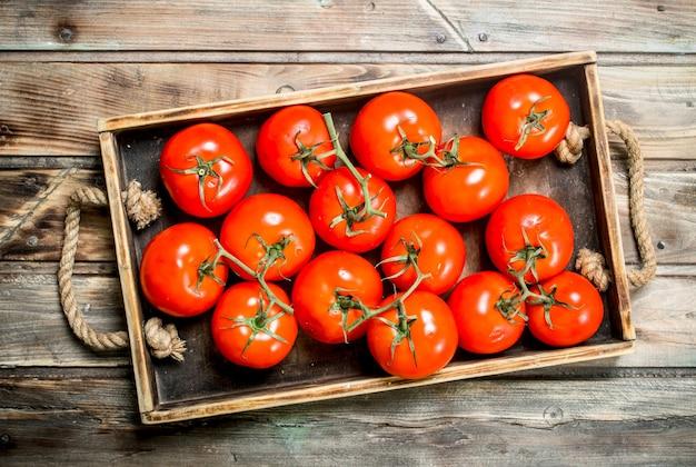 Tomates vermelhos na bandeja. na mesa de madeira