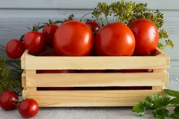 Tomates vermelhos na caixa de madeira