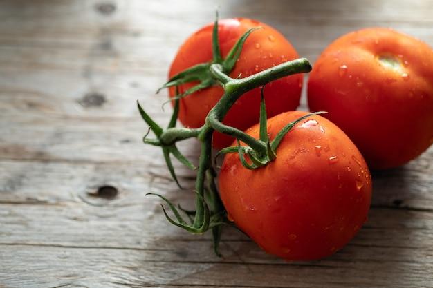 Tomates vermelhos naturais, tomates cereja em um fundo de madeira