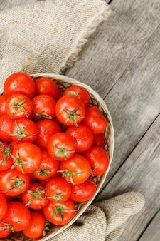 Tomates vermelhos pequenos em uma cesta de vime em uma tabela de madeira velha. cereja madura e suculenta