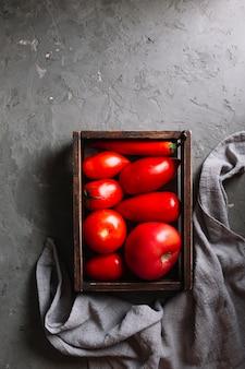 Tomates vermelhos saborosos em uma cesta plana leigos
