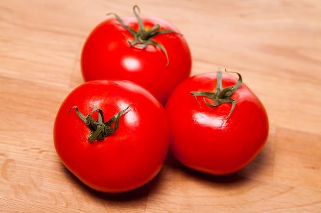 Tomates vermelhos sobre a superfície de madeira