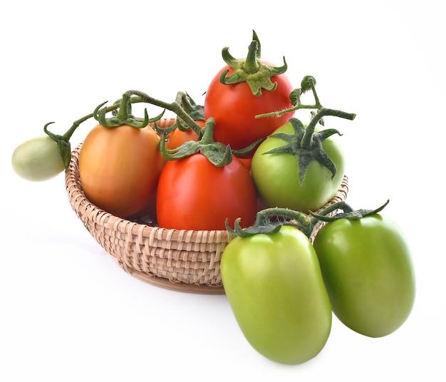 Tomates vermelhos, verdes e amarelos em uma cesta em fundo branco