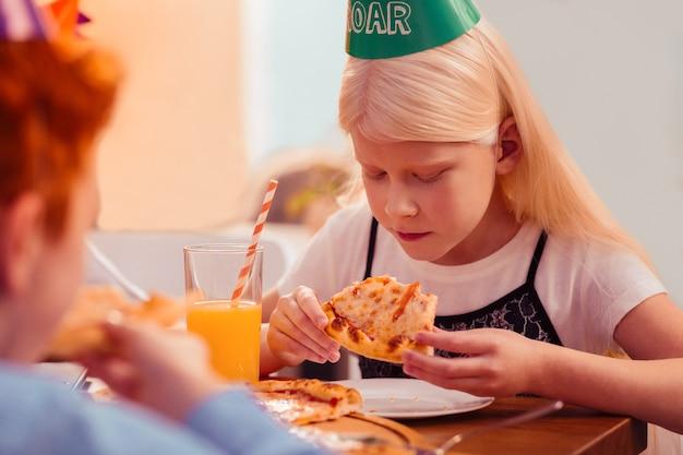 Tome cuidado. pequena mulher séria curvando a cabeça enquanto vai jantar