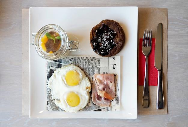 Tome o café da manhã com ovos fritos, bacon, panqueca e iogurte na placa branca.