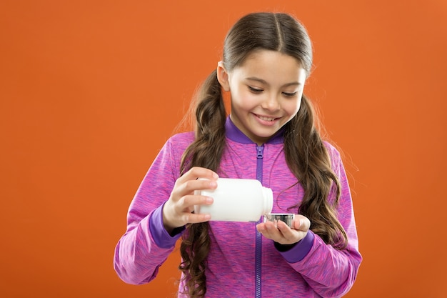 Tome suplementos vitamínicos. menina segurar o frasco de medicamentos. conceito de vitamina e medicamento. a menina criança toma medicamentos. necessita de suplementos vitamínicos. para uma flora digestiva saudável. suplemento dietético para crianças.