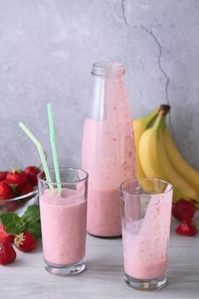 Tome uma bebida e sirva um smoothie de banana com morango preparado na hora