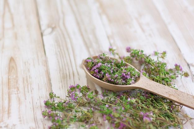 Tomilho em uma colher de pau em uma vista lateral do fundo de madeira gasto branco. condimentos, especiarias, ervas medicinais, aromaterapia.