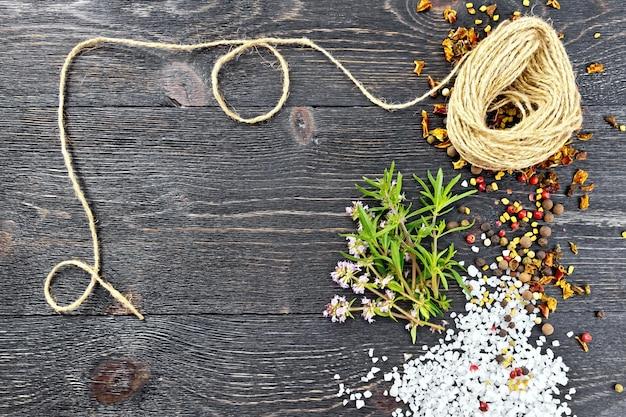 Tomilho fresco com folhas verdes e flores rosas, sal, pimenta, sementes de feno-grego e um rolo de barbante contra uma placa de madeira preta