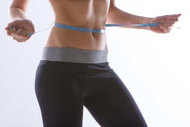 Tonificado estômago close-up sobre um fundo branco. garota mede sua cintura com uma fita de centímetro.