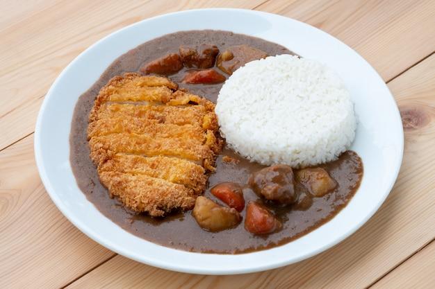 Tonkatsu, costeleta de porco frita japonesa no topo com curry em prato branco na mesa de madeira