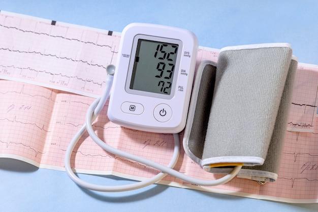 Tonômetro elétrico branco em um cardiograma e valor de alta pressão. conceito de medicina.