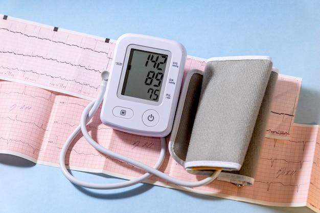 Tonômetro elétrico branco em um eletrocardiograma com. conceito de medicina.