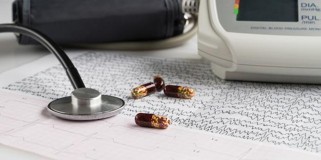Tonômetro elétrico moderno e um estetoscópio em um gráfico de eletrocardiograma. monitor doméstico de pressão arterial
