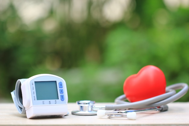 Tonômetro médico para medir a pressão arterial com estetoscópio e coração vermelho sobre fundo verde, conceito de cuidados de saúde