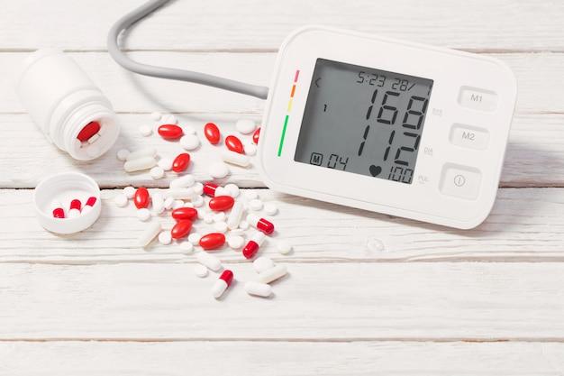 Tonômetro moderno com pílulas na mesa de madeira