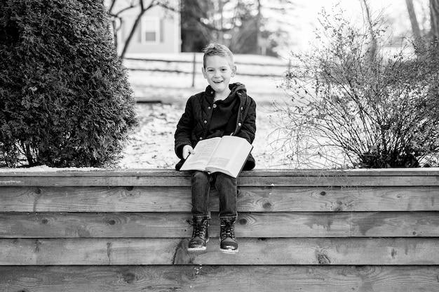 Tons de cinza de um menino feliz sentado em uma cerca de madeira e lendo um livro em um parque