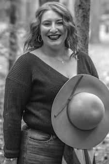 Tons de cinza de uma mulher sorridente com um chapéu em uma floresta