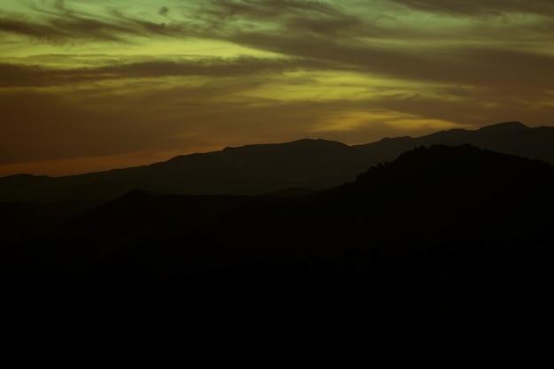 Tons de verde e amarelos do céu nublado