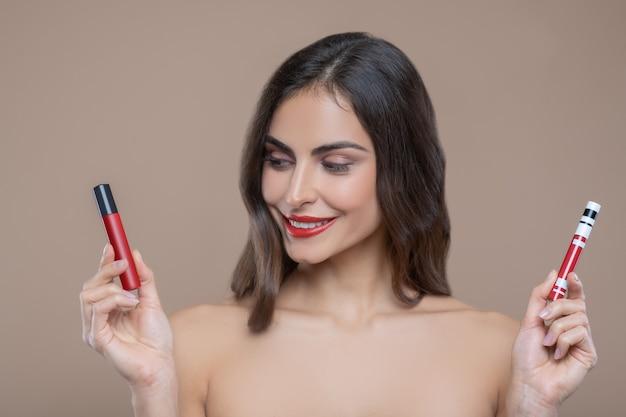Tons de vermelho. mulher bonita e seminua sorridente segurando dois tons de brilho labial vermelho escolhendo