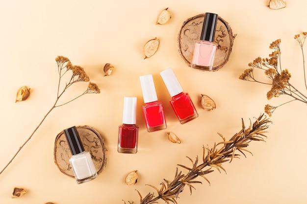 Tons nude delicados e vermelhos brilhantes em uma superfície natural neutra do layout