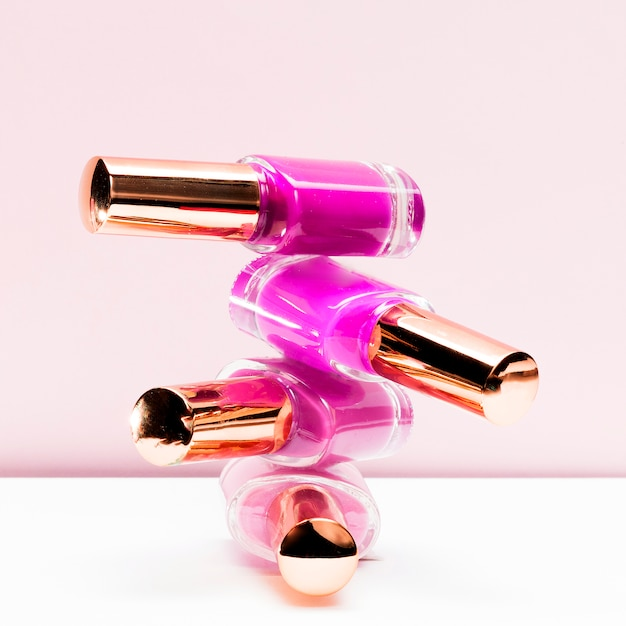Tons rosa de garrafa de esmalte de unha empilhada