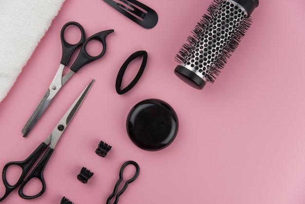 Toolse cabeleireiro profissional. equipamento do estilista de cabelo em fundo rosa.