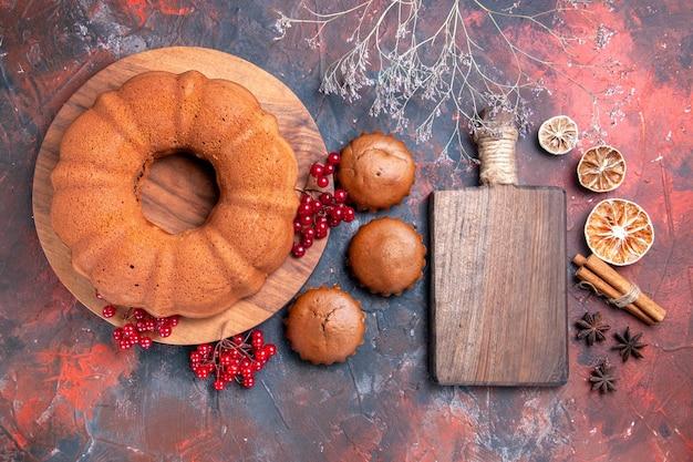Top close-up de bolo de limão, canela, anis estrelado, tábua de madeira com cupcakes de groselha