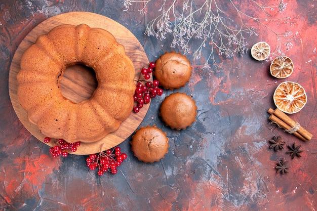 Top close-up de bolo de limão em bastões de canela bolo de anis estrelado com saborosos cupcakes de groselha