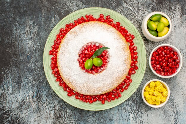 Top close-up de bolo e doces um prato de bolo com tigelas de romã com doces de frutas cítricas