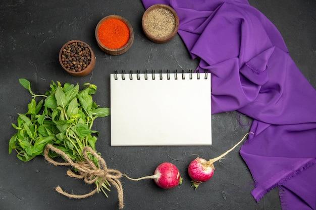 Top close-up de especiarias, caderno branco, ervas, rabanete, especiarias coloridas e a toalha de mesa roxa
