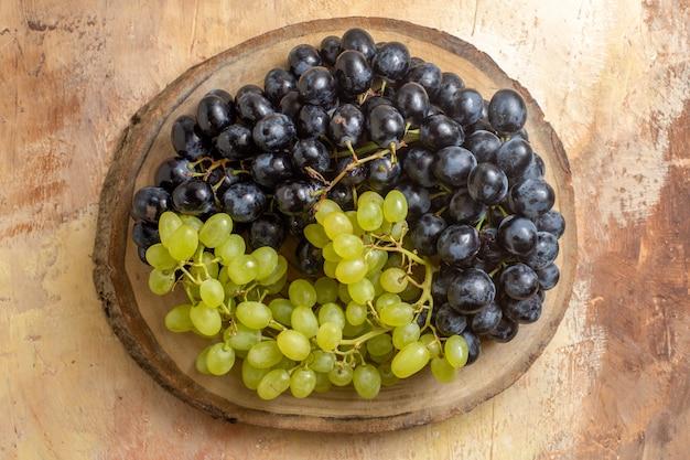 Top close-up de uvas com cachos de uvas verdes e pretas na tábua de corte