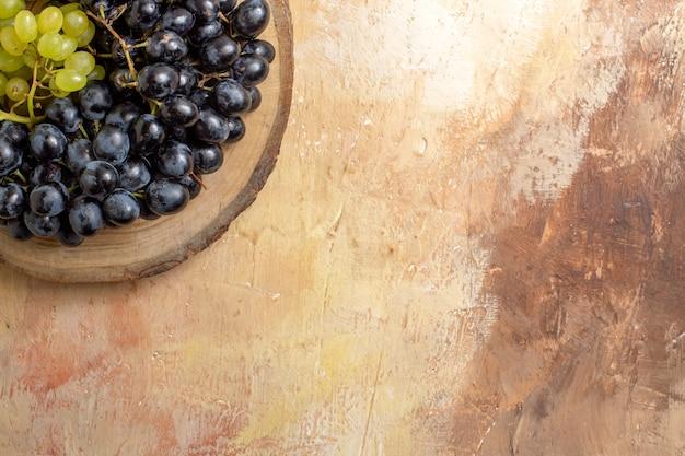 Top close-up de uvas com cachos de uvas verdes e pretas na tábua de madeira