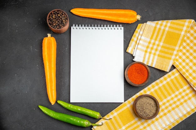 Top close-up de vegetais caderno quadriculado toalha de mesa cenoura pimenta pimenta temperos