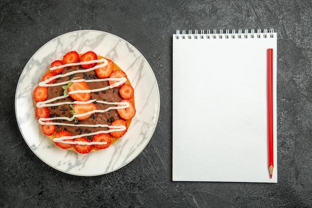 Top close-up do bolo com morangos, caderno branco e lápis vermelho ao lado do bolo com morangos e chocolate na mesa escura