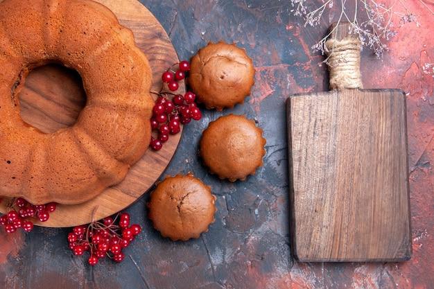 Top close-up view cake um apetitoso bolo com cupcakes de groselha ao lado da tábua de corte