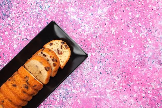 Top close view delicioso bolo doce e gostoso fatiado na mesa rosa.