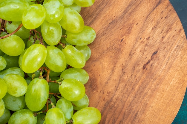 Top close view uvas verdes frescas frutas suculentas maduras na mesa azul escuro.